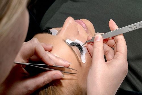 Wimpernverlängerung mit Volumenwimpern eine Stylistin fügt mit einer Pinzette Wimpern am Auge ein